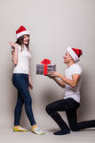 Couple share Chistmas gift. Surprised girl on gray background royalty free stock photography