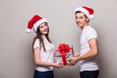 Couple share christmas gift on grey background. Happy couple share christmas gift on grey background royalty free stock photos