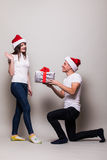 Couple share christmas gift. Surprised girl on gray background royalty free stock photo