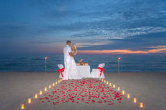 Couple share a romantic dinner with candles. Young couple share a romantic dinner with candles, torches and way or rose petals at sea sandy beach against sunset stock photo