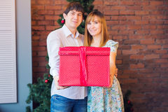 Couple Sharing Christmas Present. Young family embracing and holding red gift box at home with decorations Stock Photo