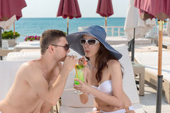 Couple Sharing Drink on Deck of Beach Resort Stock Photo