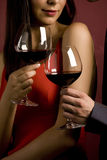 Couple sharing a glass of red wine. Mid adult Caucasian male and female hands toasting wine glasses Stock Images