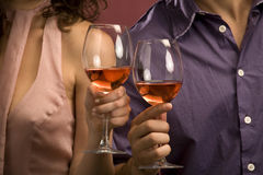 Couple sharing a glass of red wine. Mid adult Caucasian male and female hands toasting wine glasses Stock Photography
