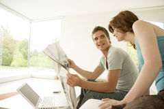 Couple Sharing Newspaper at Home Royalty Free Stock Photography