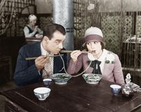 Couple sharing a noodle in a restaurant Royalty Free Stock Image