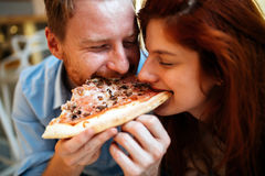 Couple sharing pizza and eating Stock Photos