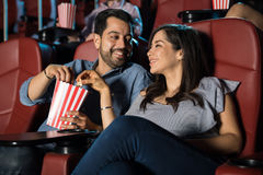 Couple sharing popcorn at the movies. Happy Hispanic couple watching a movie at the cinema theater and sharing some popcorn Royalty Free Stock Images