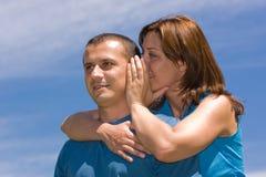 Couple sharing secrets. Young couple sharing secrets under blue sky Stock Image