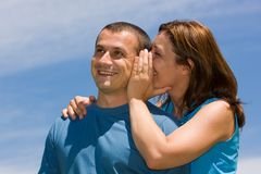 Couple sharing secrets. Young couple sharing secrets under blue sky Stock Photography