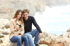 Couple sharing a smart phone on the beach on holidays. Couple sharing a smart phone on the beach on winter holidays with the ocean in the background Royalty Free Stock Photo