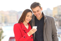 Couple sharing smart phone in winter. Couple sharing a smart phone watching media content outdoors in winter Stock Photo