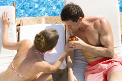 Couple sharing tropical drink on lounge chairs at poolside Royalty Free Stock Image