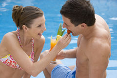 Couple sharing tropical drink at poolside Royalty Free Stock Photography