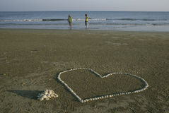 A couple with shell heart. Young couple waking on the beach at the ocean Royalty Free Stock Image