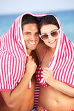 Couple Sheltering From Sun On Beach Holiday Stock Photography