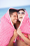 Couple Sheltering From Sun On Beach Holiday Stock Images