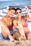 Couple Sheltering From Sun Under Beach Umbrella. Smiling To Camera Stock Photo