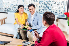 Couple with shop assistant in furniture store Stock Photography