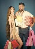 Couple of shopaholics. Girl and bearded man hold present pack, cyber Monday. Royalty Free Stock Photos