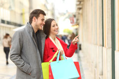 Couple of shoppers shopping in the street Royalty Free Stock Image