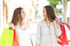 Couple of shoppers talking walking in the street. Front view portrait of a happy couple of shoppers talking holding shopping bags walking in the street royalty free stock photos