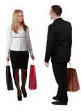 Couple shopping. A men and a women with shopping bags passing by themselves, against a white background Royalty Free Stock Photo