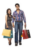 Couple with Shopping Bag. Happy young couple with shopping bags over white background royalty free stock photo