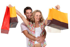 Couple with shopping bags. Happy couple with shopping bags held in air Royalty Free Stock Photo