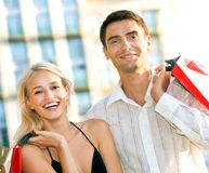 Couple with shopping bags. Young attractive happy couple with shopping bags outdoors royalty free stock image