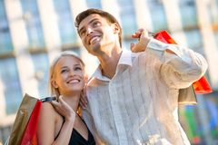 Couple with shopping bags. Young attractive happy couple with shopping bags outdoors stock photos