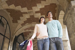 Couple With Shopping Bags Through Archway Royalty Free Stock Photos