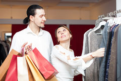Couple with shopping bags choosing sweater Stock Photos