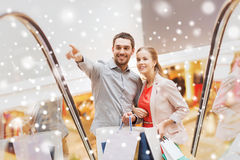 Couple with shopping bags on escalator in mall. Sale, consumerism and people concept - happy young couple with shopping bags rising on escalator and pointing Royalty Free Stock Image