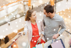 Couple with shopping bags on escalator in mall. Sale, consumerism and people concept - happy young couple with shopping bags rising on escalator and talking and Royalty Free Stock Photography