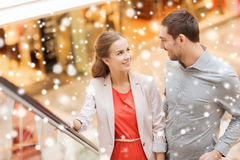 Couple with shopping bags on escalator in mall. Sale, consumerism and people concept - happy young couple with shopping bags rising on escalator and talking and Royalty Free Stock Image
