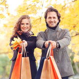Couple with shopping bags. Happy smiling couple with shopping bags in autumn park Stock Image