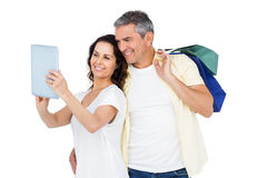 Couple with shopping bags looking at PC tablet Royalty Free Stock Photo