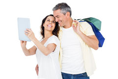 Couple with shopping bags looking at PC tablet Stock Photos