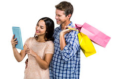 Couple with shopping bags looking at tablet PC Stock Images