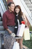Couple With Shopping Bags In Mall. Happy middle aged couple with shopping bags in mall Royalty Free Stock Images