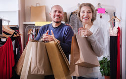 Couple with shopping bags. Mature couple with shopping bags in their hands in boutique Royalty Free Stock Photography