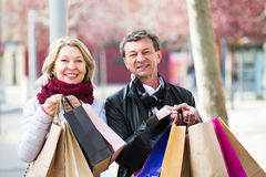 Couple with shopping bags outdoors. Portrait of elderly couple with shopping bags outdoors Stock Photography