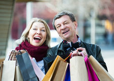 Couple with shopping bags outdoors. Portrait of elderly happy couple with shopping bags outdoors Royalty Free Stock Photography