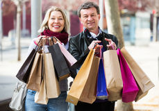 Couple with shopping bags outdoors. Portrait of mature happy couple with shopping bags outdoors Royalty Free Stock Image