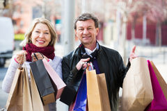 Couple with shopping bags outdoors. Portrait of senior couple with shopping bags outdoors Stock Image