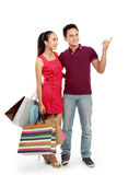 Couple with shopping bags pointing Royalty Free Stock Image