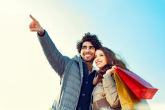 Couple with Shopping Bags Pointing into Distance Royalty Free Stock Photo