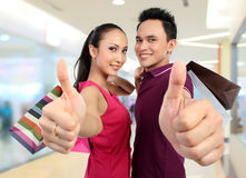 Couple with shopping bags showing thumb up Stock Photo