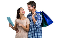 Couple with shopping bags using digital tablet. Against white background Royalty Free Stock Photography